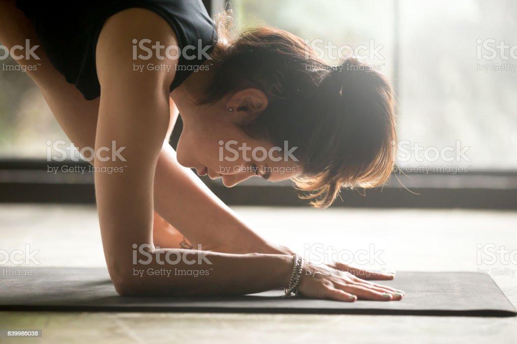 Young attractive woman in Parsvottanasana, Pyramid pose, studio background stock photo