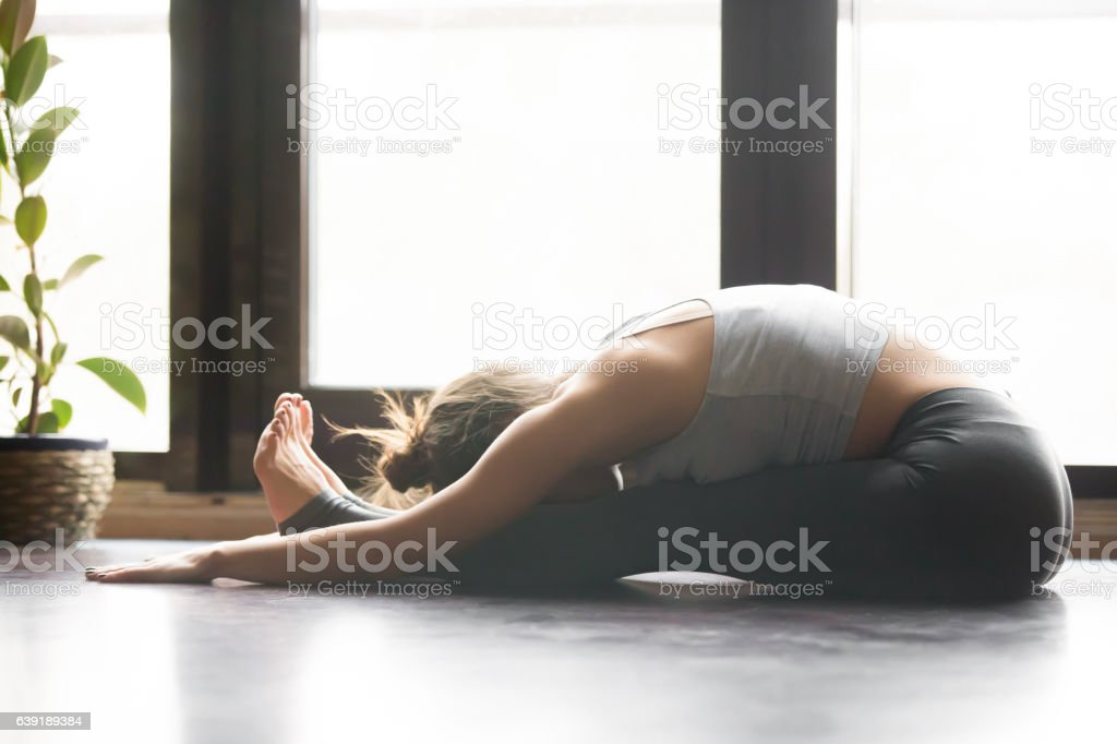 Young attractive woman in paschimottanasana pose, home interior stock photo