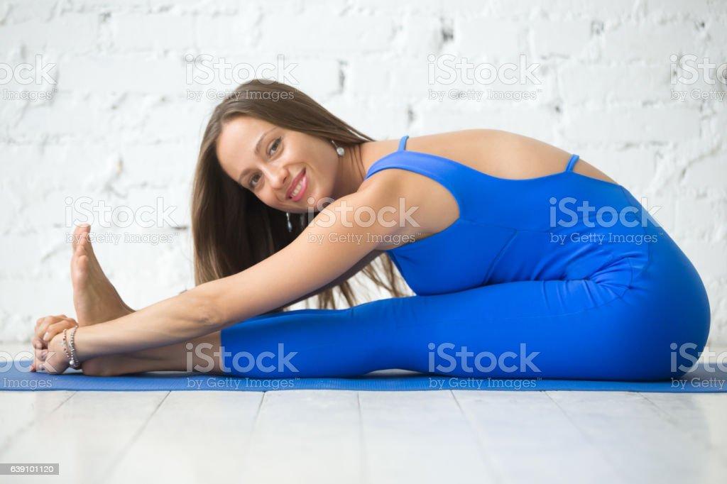 Young attractive woman in paschimottanasana pose, white studio stock photo