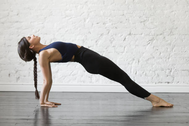 Young attractive woman in Purvottanasana pose, studio background Young attractive woman practicing yoga, stretching in Purvottanasana exercise, Upward Plank pose, working out, wearing sportswear, black top and pants, indoor full length, studio background upward facing dog position stock pictures, royalty-free photos & images