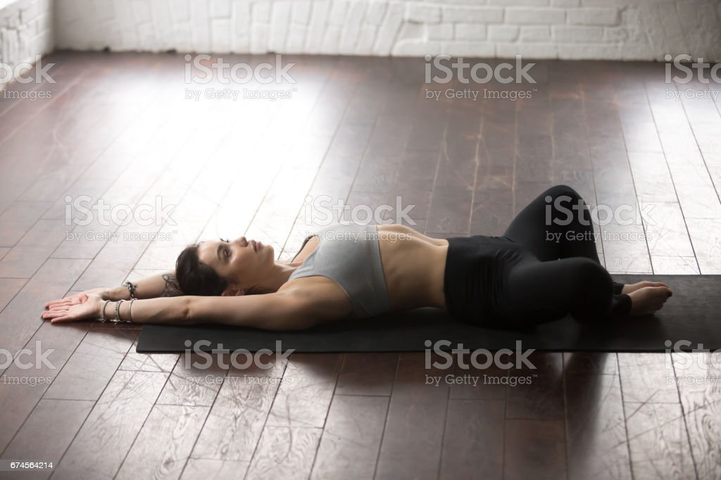 Young attractive woman in Reclined Butterfly pose, white loft st stock photo