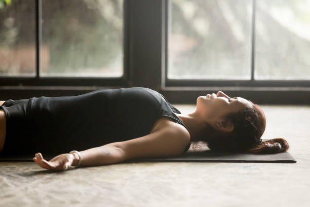 Young attractive woman in Savasana pose, studio background stock photo