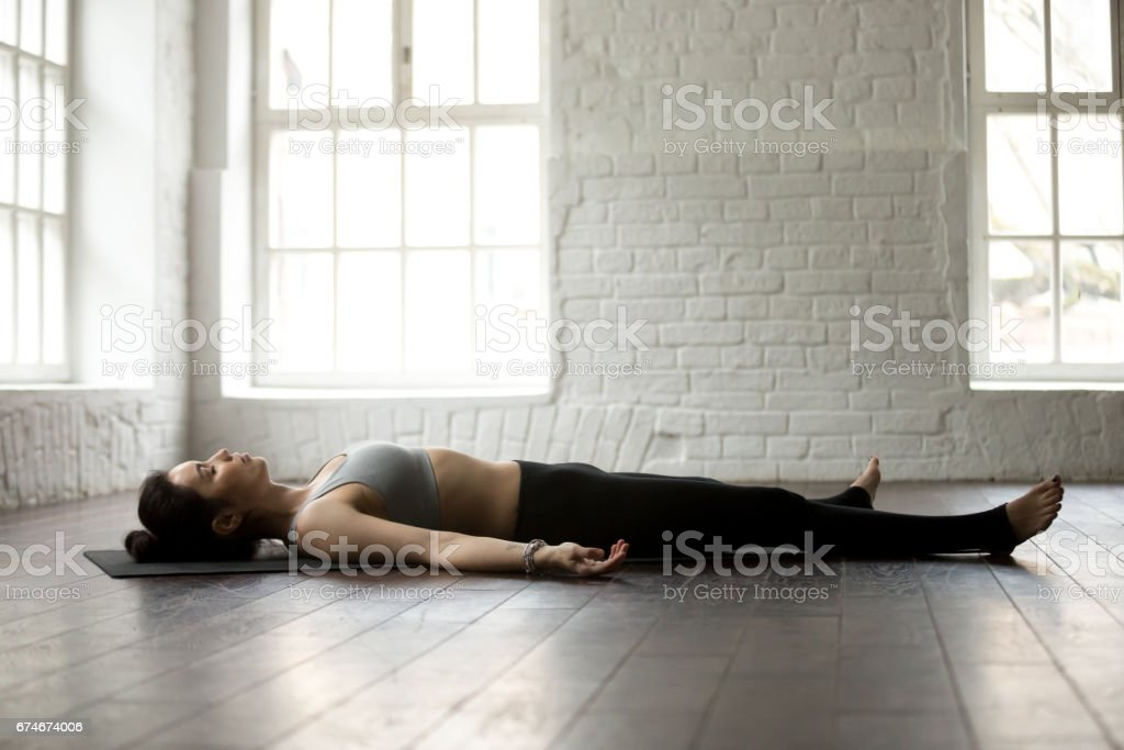Young attractive woman in Savasana pose, white loft studio backg stock photo