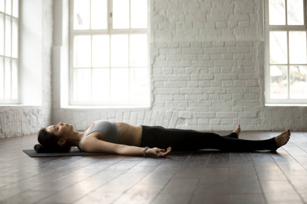 Young attractive woman in Savasana pose, white loft studio backg Young attractive yogi woman practicing yoga exercises concept, lying in Dead Body, Savasana, Corpse pose, resting after working out, wearing sportswear, full length, white loft studio background lying on back stock pictures, royalty-free photos & images