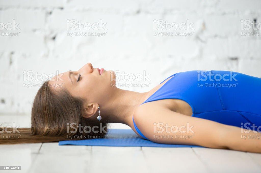 Young attractive woman in Savasana pose, white studio background stock photo