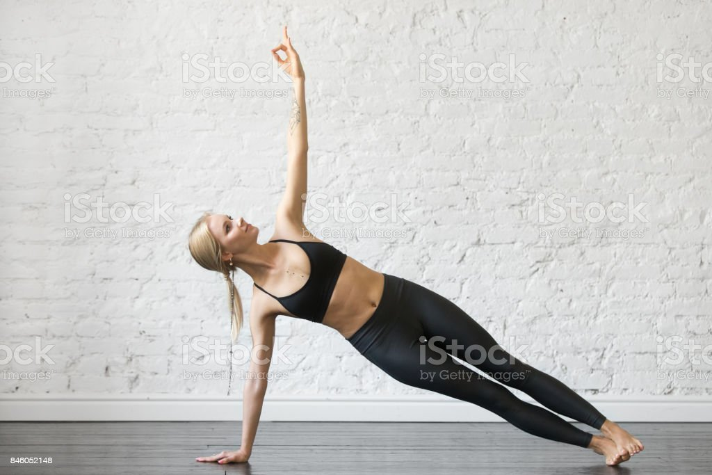 Young attractive woman in Side Plank pose, studio background stock photo