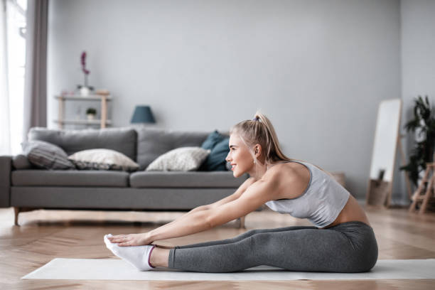 Young attractive woman in sportswear doing exercise in living room. stock photo