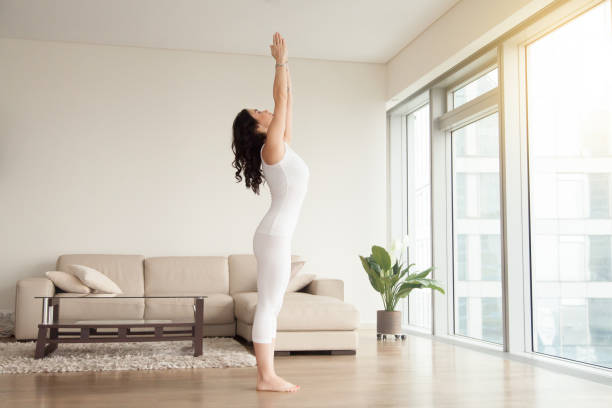 Young attractive woman in Tadasana pose, cozy hotel living room Young attractive woman practicing yoga at home, standing in mountain exercise, Tadasana pose, working out, wearing white clothes, indoor full length, in the center of living room namaskard geothermal area stock pictures, royalty-free photos & images