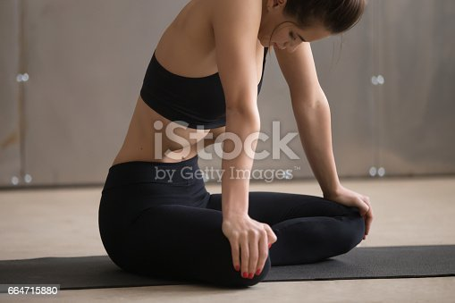 istock Young attractive woman in Uddiyana Bandha pose, grey studio back 664715880