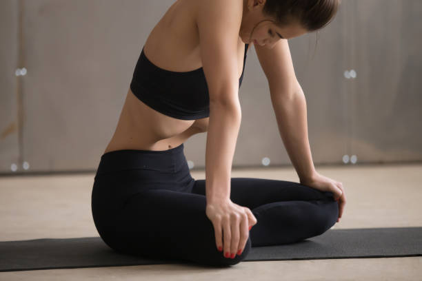 Young attractive woman in Uddiyana Bandha pose, grey studio back Young attractive sporty woman practicing yoga, sitting in Sukhasana pose, making Upward Abdominal Lock, Uddiyana Bandha exercise, working out, black sportswear, cool urban style, close up, grey studio abdominal muscle stock pictures, royalty-free photos & images