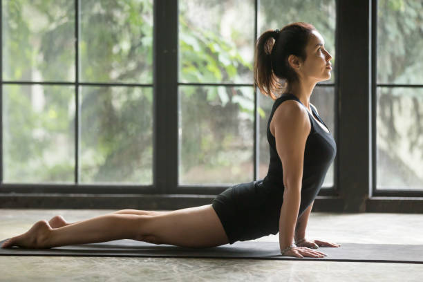 Young attractive woman in upward facing dog pose, studio background Young attractive woman practicing yoga at home, stretching in Urdhva mukha shvanasana exercise, upward facing dog pose, working out wearing sportswear, black shorts and top, indoor full length, studio namaskard geothermal area stock pictures, royalty-free photos & images