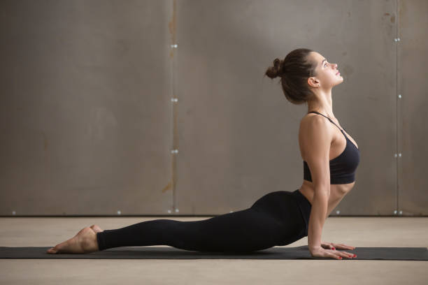 Young attractive woman in Urdhva mukha shvanasana pose, grey stu Young attractive yogi woman practicing yoga, stretching in Urdhva mukha shvanasana exercise, upward facing dog pose, working out, wearing black sportswear, cool urban style, full length, grey studio namaskard geothermal area stock pictures, royalty-free photos & images