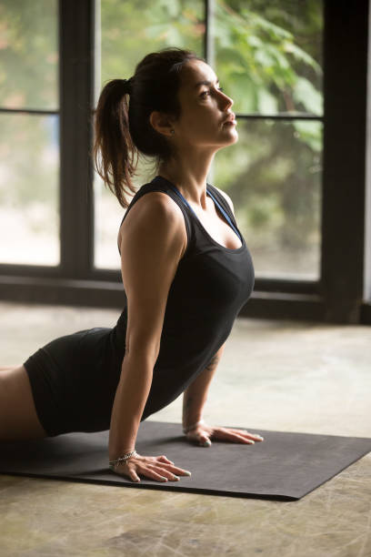 Young attractive woman in Urdhva mukha shvanasana pose, studio background Young attractive sporty woman practicing yoga, stretching in upward facing dog exercise, Urdhva mukha shvanasana pose, working out, wearing sportswear, black top, indoor, window background, side view upward facing dog position stock pictures, royalty-free photos & images