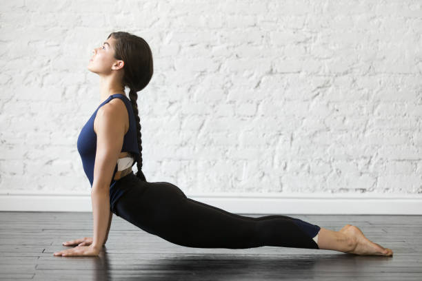 Young attractive woman in Urdhva mukha shvanasana pose, studio background Young attractive woman practicing yoga, stretching in Urdhva mukha shvanasana exercise, upward facing dog pose, working out wearing sportswear black top and pants, indoor full length studio background upward facing dog position stock pictures, royalty-free photos & images