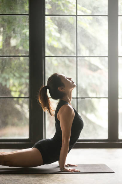 Young attractive woman in Urdhva mukha shvanasana pose, window background Young attractive woman practicing yoga, stretching in upward facing dog exercise, Urdhva mukha shvanasana pose, working out, wearing black sportswear, indoor close up image, window background upward facing dog position stock pictures, royalty-free photos & images