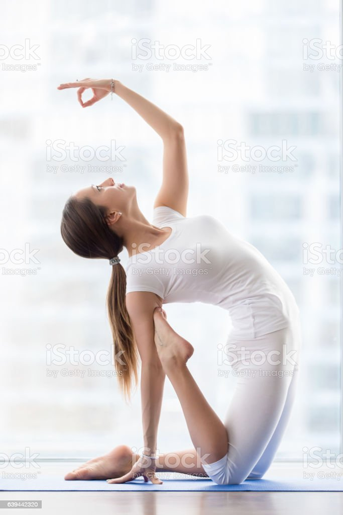Young attractive woman in Ustrasana pose with mudra, floor windo stock photo