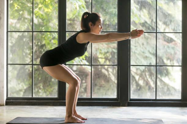 young attractive woman in utkatasana pose, studio background - peso mosca foto e immagini stock