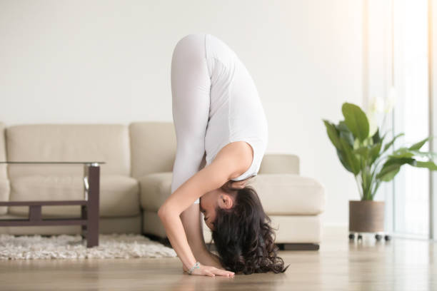 Young attractive woman in uttanasana pose, at hotel living room Young attractive woman practicing yoga at home, standing in uttanasana exercise, head to knees pose, standing forward bend, working out, wearing white clothes, indoor full length, living room namaskard geothermal area stock pictures, royalty-free photos & images