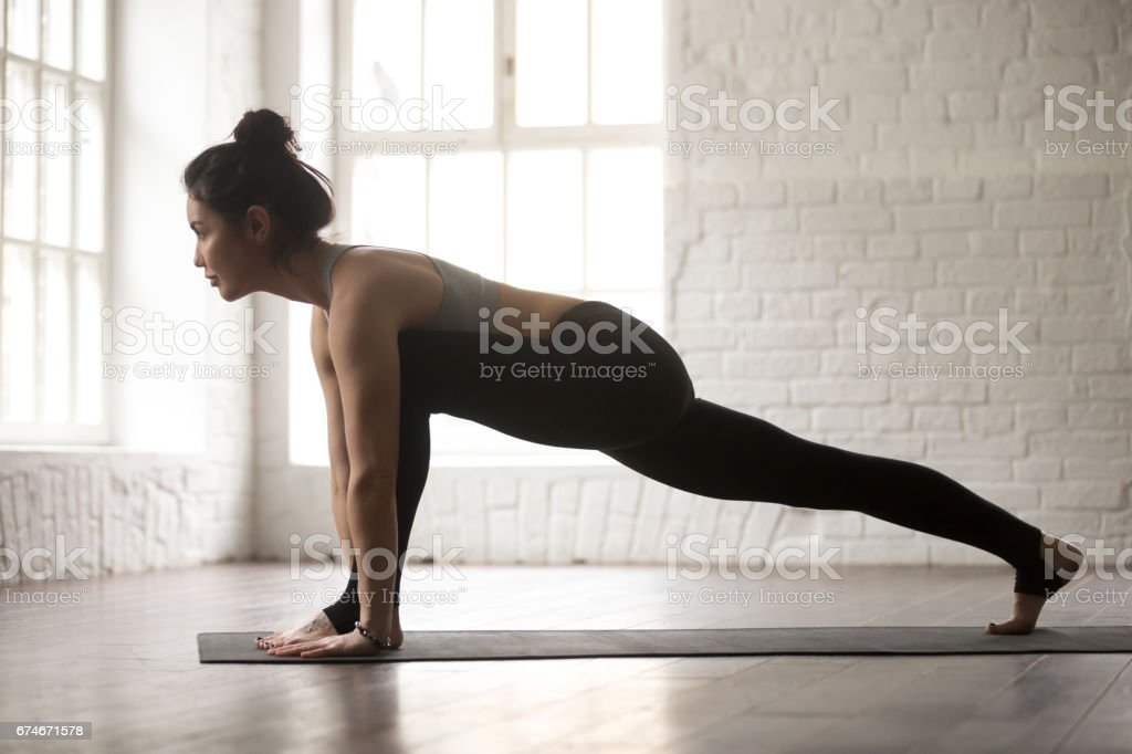 Young attractive woman in Utthan Pristhasana pose, white loft st stock photo