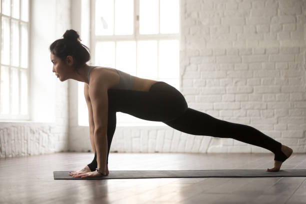 young attractive woman in utthan pristhasana pose, white loft st - lunge stock photos and pictures
