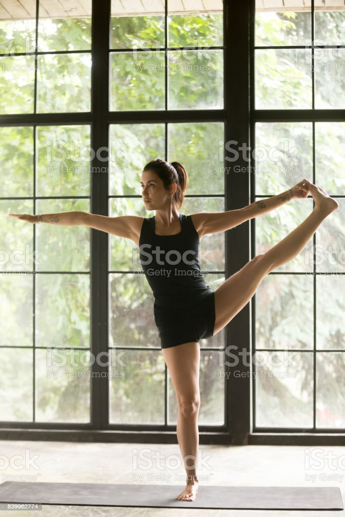 Young attractive woman in Utthita Hasta Padangustasana pose, studio background stock photo