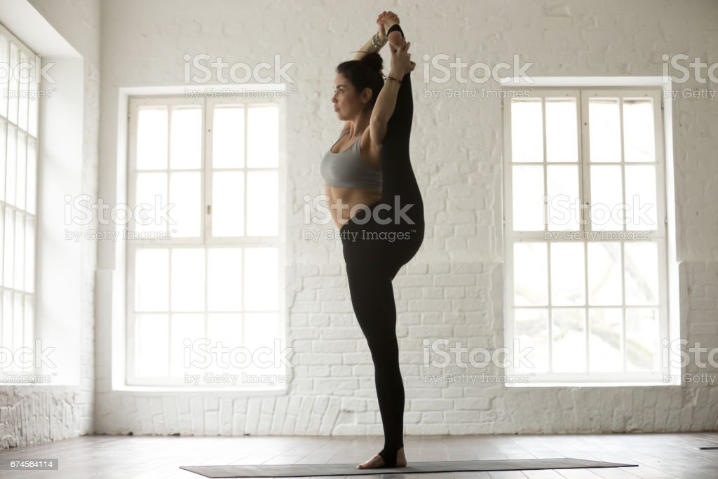 Young attractive woman in Variation of Utthita Hasta Padangushth stock photo