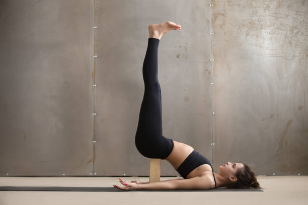 Young attractive woman in Viparita Karani pose with block, studi Young attractive yogi woman practicing yoga, standing in Viparita Karani exercise, using wooden block, working out, wearing black sportswear, cool urban style, full length, grey studio background shoulder stand stock pictures, royalty-free photos & images