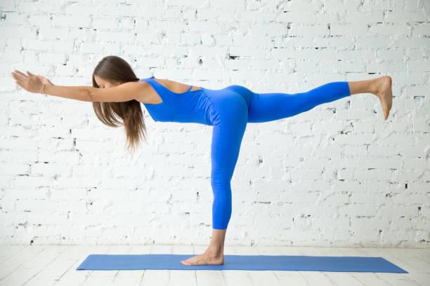 young attractive woman in virabhadrasana iii pose, white studio - jumpsuit blau stock-fotos und bilder