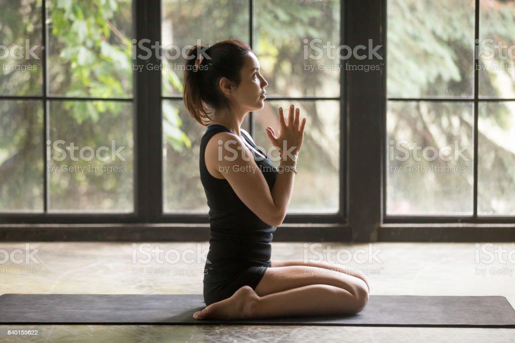 Young attractive woman in Virasana pose, studio background stock photo