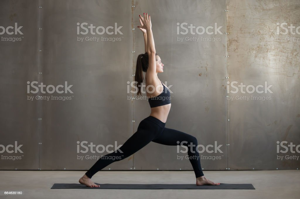 Young attractive woman in Warrior one pose, grey studio backgrou stock photo