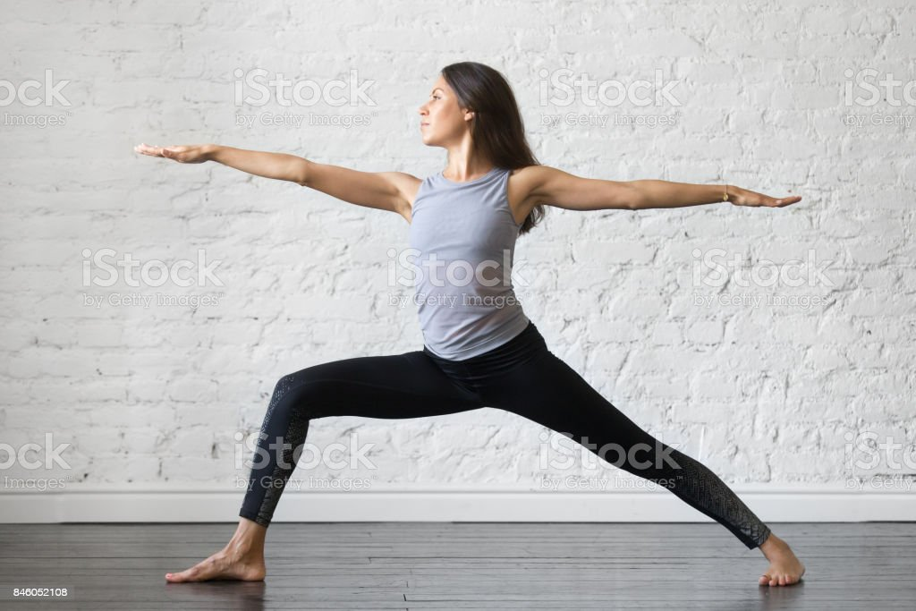 Young attractive woman in Warrior two pose, studio background stock photo