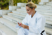 Young attractive woman in white kimono with black belt. Sport woman sitting on stairs and uses smartphone outdoors. Rest after training. Martial arts