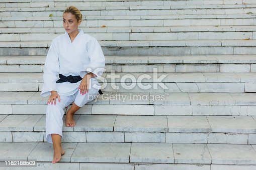 Young attractive woman in white kimono with black belt. Sport woman sitting on stairs outdoors. Martial arts
