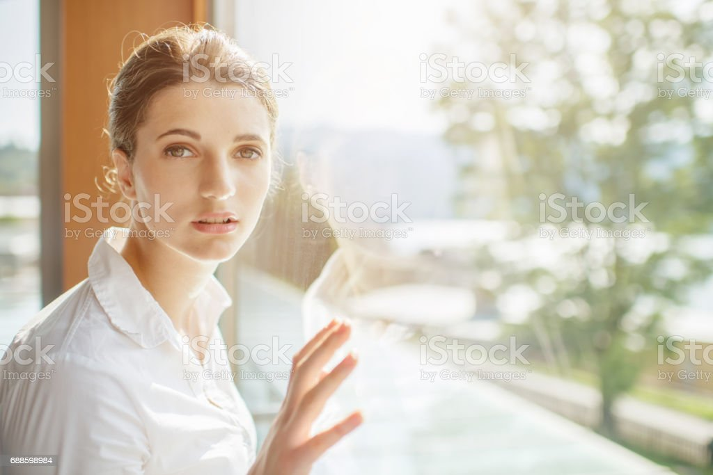 Young attractive woman leaning at window stock photo