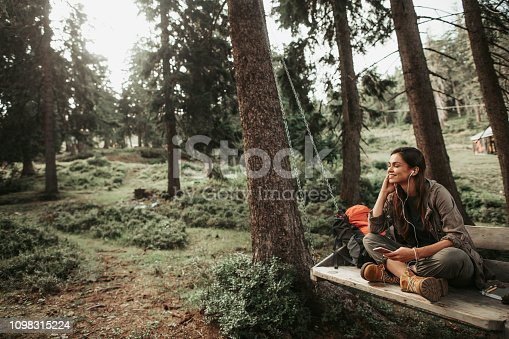 In the woods. Portrait of beautiful girl with closed eyes sitting on wooden swing and enjoying favorite song. She is smiling