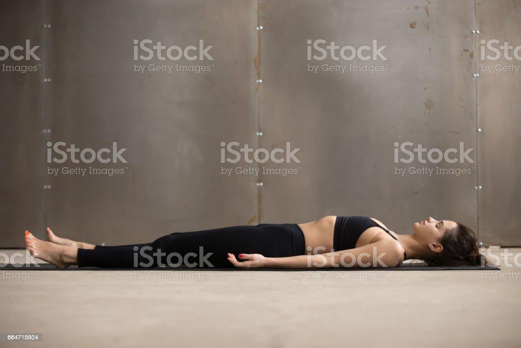 Junge attraktive Frau liegt in Savasana posiert, graues Studio backg - Lizenzfrei Aerobic Stock-Foto