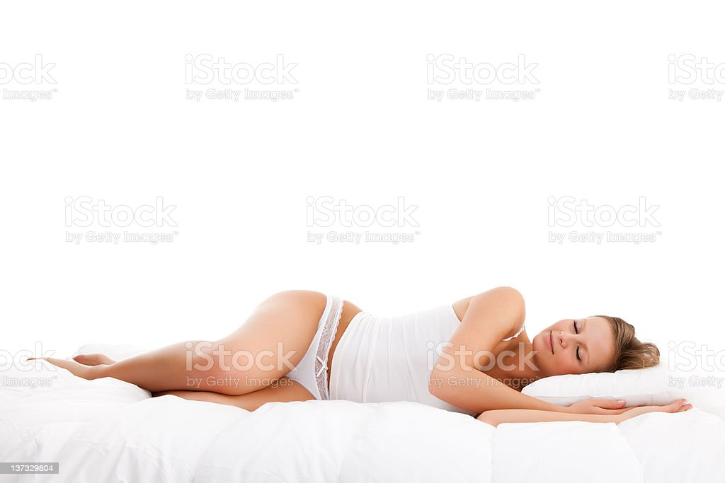 Young, attractive woman lying on bed - isolated royalty-free stock photo