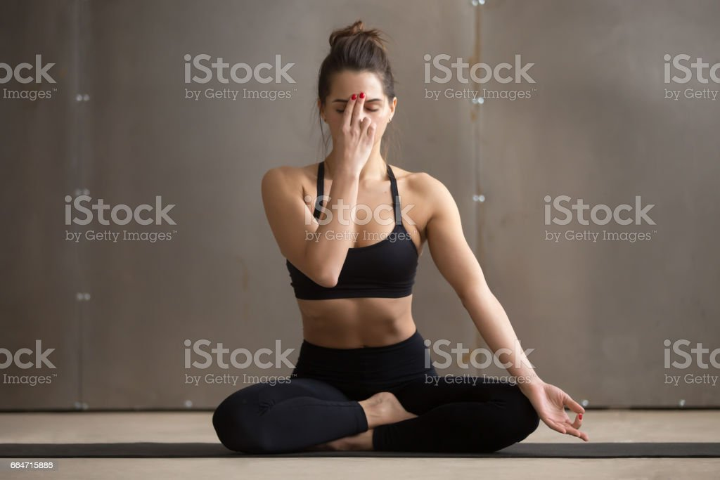 Young attractive woman making Alternate Nostril Breathing, grey stock photo