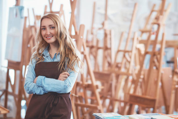 Young attractive woman on the background of easels stock photo