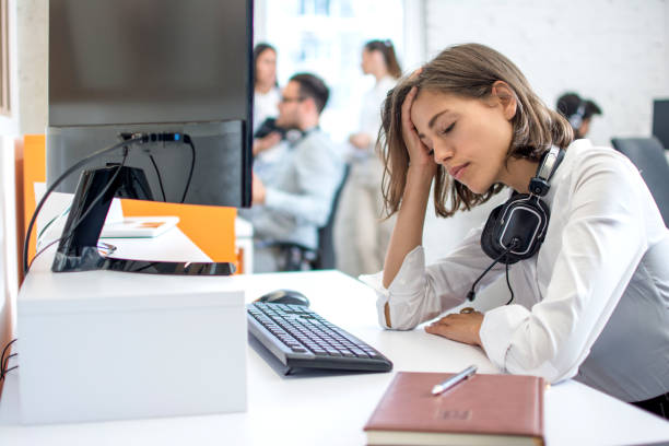 Young attractive woman operator with headset over neck suffering from headache stock photo