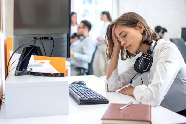 Junge attraktive Frau Betreiber mit Headset über Hals leidet unter Kopfschmerzen – Foto
