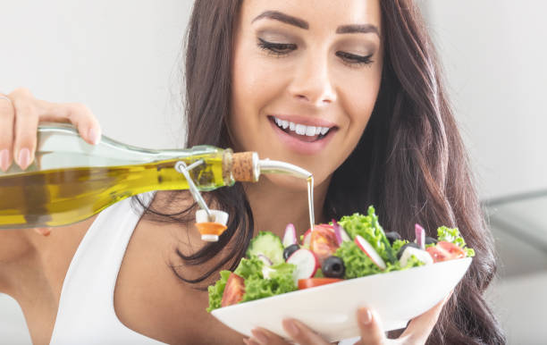 young attractive woman pours olive oil into a healthy vegetable salad stock photo