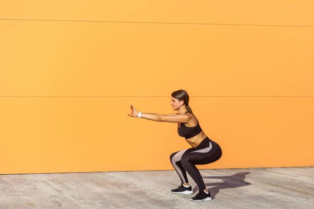 joven mujer atractiva practicando fitness, haciendo ejercicio de sentadilla de peso corporal, postura de silla de yoga, hacer ejercicio, usar pantalones negros y top negros, - agacharse fotografías e imágenes de stock