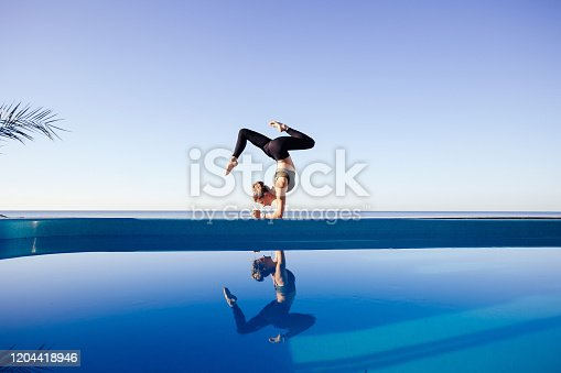 Young attractive woman practicing yoga stand in Adho Mukha Vrksasana exercise, Downward facing Tree pose, working out by the pool, above the beach, relaxing against blue sky. Health and beauty concept