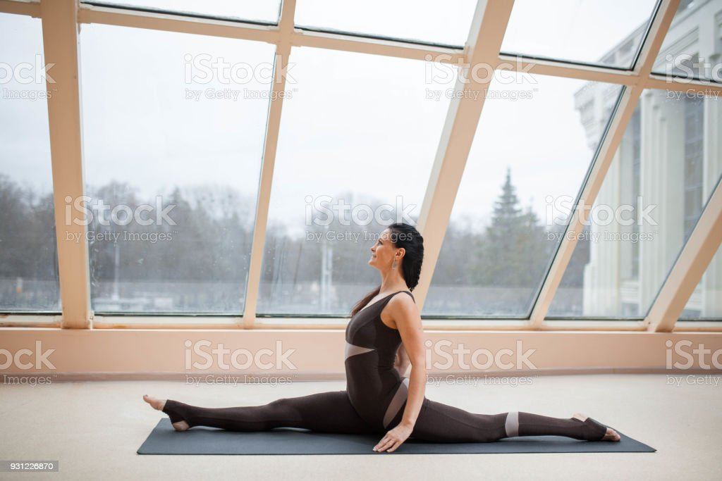 Young attractive woman practicing yoga, sitting in Monkey God, Splits exercise, Hanumanasana pose, working out, wearing sportswear, indoor full length, large windows background. stock photo