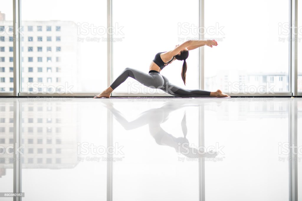 Young attractive woman practicing yoga, standing in anjaneyasana exercise, Horse rider pose, working out, wearing sportswear, sport bra against panoramic windows stock photo