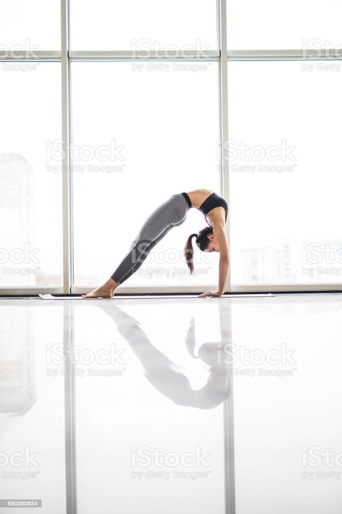 Young attractive woman practicing yoga, stretching in Elbow Bridge exercise, Urdhva Dhanurasana pose against panoramic windows stock photo