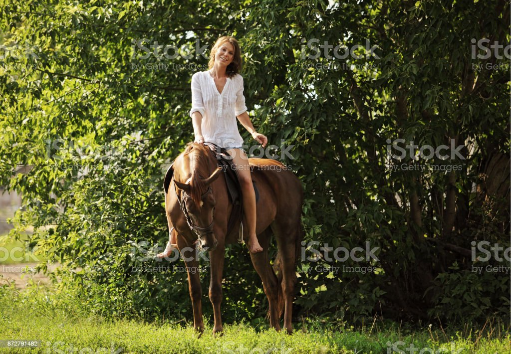Young attractive woman relaxing horseback stock photo