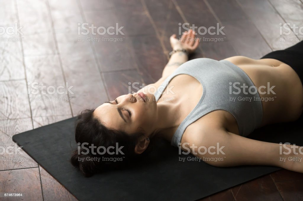 Young attractive woman relaxing in Savasana pose, white loft stu stock photo