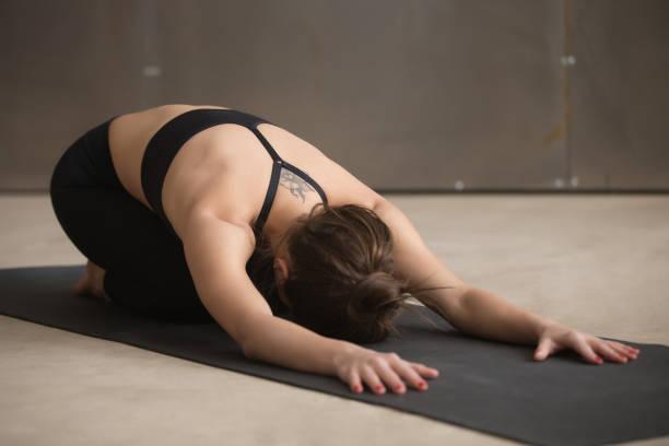 junge attraktive frau im balasana pose, graue studio bac - gymnastik tattoo stock-fotos und bilder